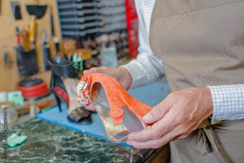 Foto op Canvas Gymnastiek Cobbler holding orange wedge heeled shoe