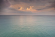 Delicate sunset over the azure sea with beautiful pastel colors. A minimalistic view of the tropical sea with the sky.