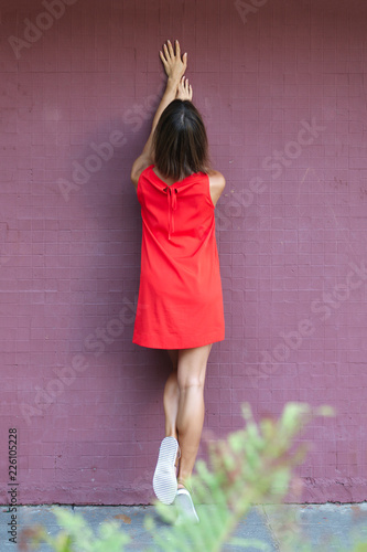 Fotografía  Full length portrait of a girl leaning against brick wall with lifted up hands