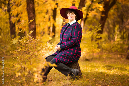 Fotografia  60 year old woman in red hat dreams in gold autumn park. Harmony