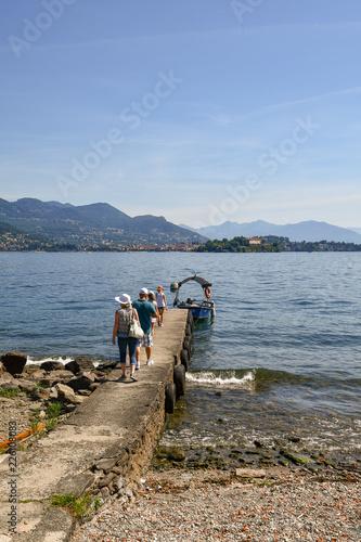 Veduta di un lago con turisti su un molo diretti verso una barca, isola e montagne sullo sfondo, Lago Maggiore, Isola dei Pescatori, Piemonte, Italia