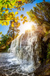 canvas print picture Landscape with waterfall in the forest and bright sun shining through the trees