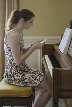 Side View Of Teenage Girl Using Mobile Phone While Sitting By Piano On Table At Home