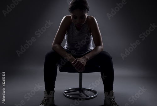 Fotografie, Obraz  Silhouette of black female athelte sitting to rest or preparing for a competition or upset over losing and failing at sports