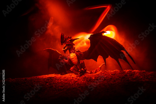 Obrazy smoki silhouette-of-fire-breathing-dragon-with-big-wings-on-a-dark-orange-background
