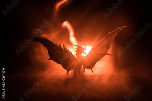 Fotografie, Obraz  Silhouette of fire breathing dragon with big wings on a dark orange background