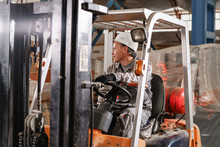 Close - Up Steering Wheel And Levers. Man Driving A Forklift Through A Warehouse In A Factory. Driver In Uniform And Protective Helmet. The Concept Of Logistics And Storage