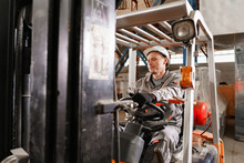 Man Driving A Forklift Through A Warehouse In A Factory. Driver In Uniform And Protective Helmet. The Concept Of Logistics And Storage