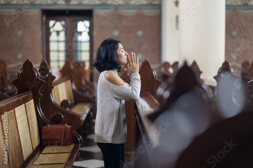 Beautiful woman praying in church Wallpaper Mural
