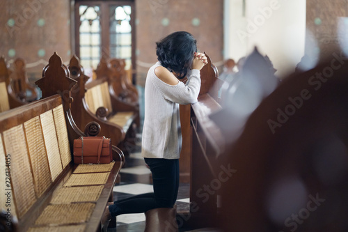 Fotomural Woman sitting with clasped hands in church