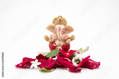 Photo Lord Ganesha Idol with rose petals on white background, ganesh chaurthi, ganesh