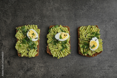 Tasty crisp rye toasts with avocado and quail egg on table, flat lay