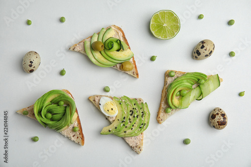 Flat lay composition with crisp avocado toasts on white background