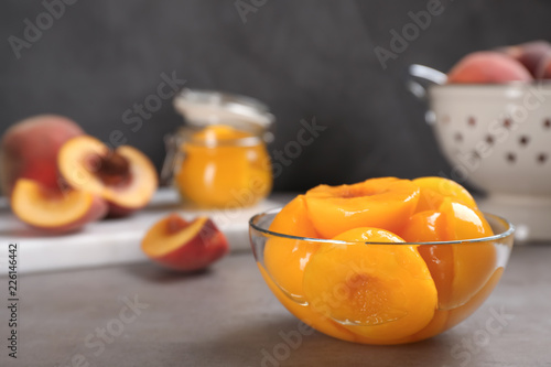 Glass bowl with conserved peach halves on grey table. Space for text