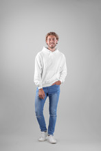 Full Length Portrait Of Man In Hoodie Sweater On Light Background. Space For Design