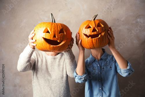 Valokuva  Women holding Halloween pumpkin head jack lanterns against color background