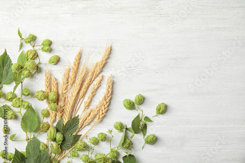 Fresh green hops and wheat spikes on white wooden background, top view with space for text. Beer production