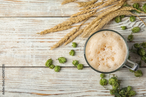 Flat lay composition with tasty beer, fresh green hops, wheat spikes and space for text on wooden background