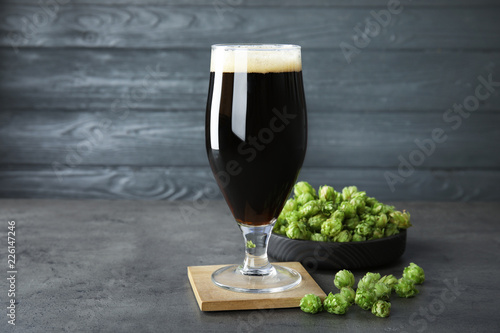 Composition with tasty beer and fresh green hops on grey table