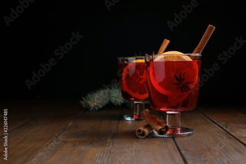 Fotobehang Cocktail Glasses with red mulled wine on wooden table against dark background. Space for text