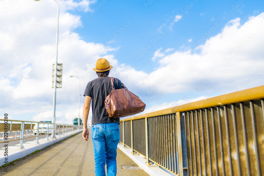 Fototapeta 橋の上を歩く男性