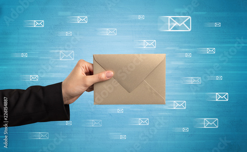 Female hand holding coloured and white envelope with blue background and message Wallpaper Mural
