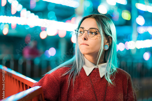 Foto op Plexiglas Amusementspark Hipster girl with blue dyed hair and sequins as freckles. Woman in red clothing and nose piercing, transparent glasses, ears tunnels, unusual hairstyle in amusement park