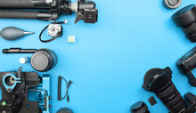 Digital Camera With Lenses And Equipment Of The Professional Photographer On Blue Paper Background.