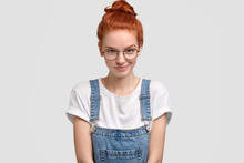 Horizontal Shot Of Pleasant Looking Ginger Young European Woman In Round Transparent Glasses, Stylish Dungarees, Poses Against White Background, Has Glad Expression. People And Emotions Concept.