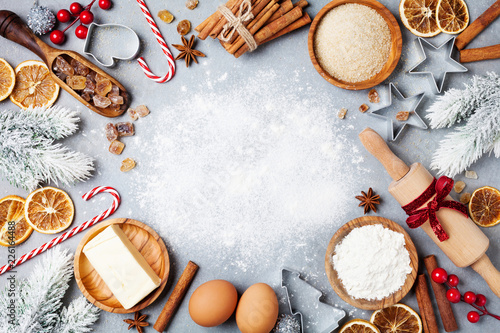 Fototapeta Ingredients for cooking christmas baking decorated with fir tree. Flour, brown sugar, eggs and spices top view. Bakery background. obraz