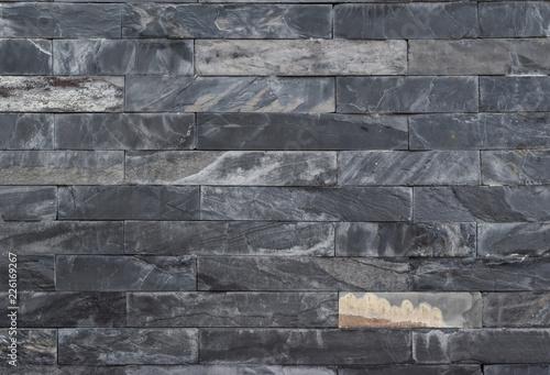 Foto op Aluminium Wand Black stone bricks wall close-up.