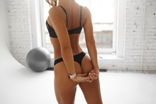 Cropped Rear View Of Unrecognizable Sexy Athletic Female Wearing Black Thongs And Bra Exercising In Loft Gym Interior, Clasping Hands Behind Her Back, Stretching Shoulders And Opening Chest