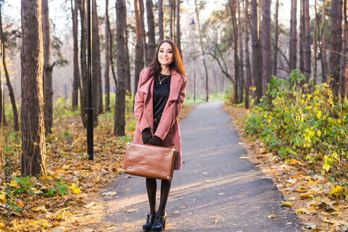 Obraz Autumn, nature and people concept - Young beautiful woman in grey coat in fall nature - fototapety do salonu