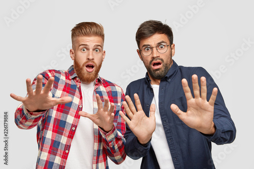 Valokuva  Photo of two men have scared expressions, make frightened gesture with plams, try to defend from something bad, exclaim with fear, ask not come close, stand against white background