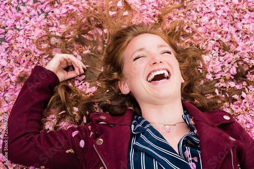 Jeune femme riant dans les fleurs Wallpaper Mural