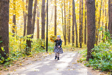 Autumn, Happiness And People Concept - Child Running Through Autumn Park With Yellow Leaves In Her Hands