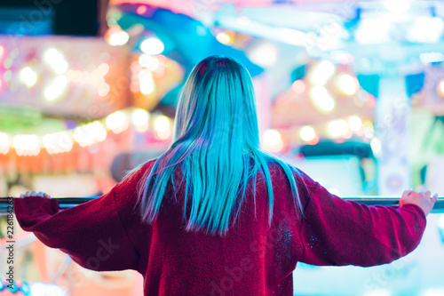Tuinposter Amusementspark Girl with dyed blue hair standing back to camera and watching rotation of attractions in amusement park. Millennial hipster lifestyle. Night, illuminated city.