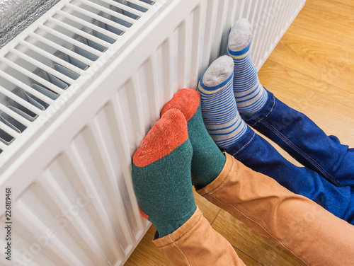 Fotografie, Obraz  Woman and child wearing colorful pair of woolly socks warming cold feet in front of heating radiator in winter time