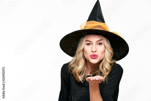 Sensual Halloween Witch Studio Portrait. Attractive young woman dressed in witch halloween costume isolated over white background blowing a kiss towards camera.