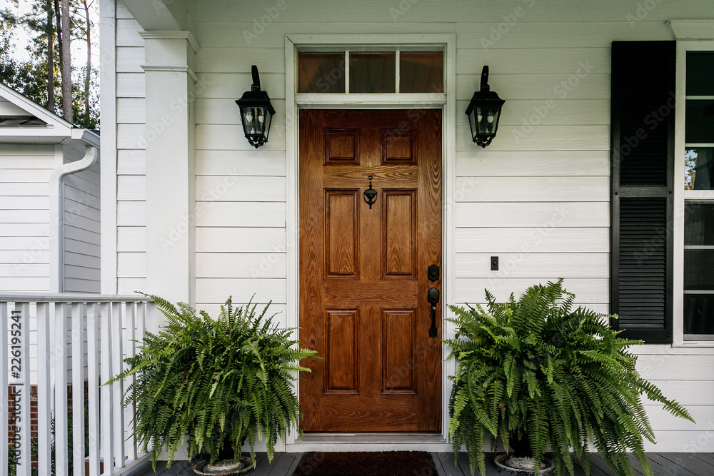 Fototapeta Brown Wood Front Door of a White Siding Southern House