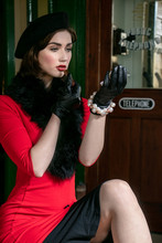 Vintage Attractive Female Wearing Red Dress And Black Beret, Sitting On Suitcases Applying Her Makeup At Train Station
