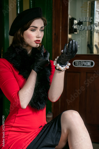 vintage attractive female wearing red dress and black beret, sitting on suitcase Wallpaper Mural