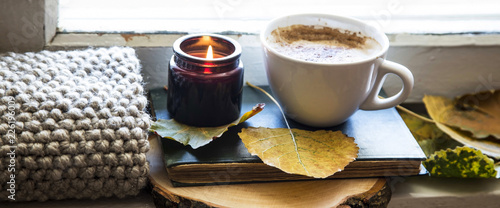 Valokuva Cozy still life autumn coffee cup with old book, scented candle and warm knitted