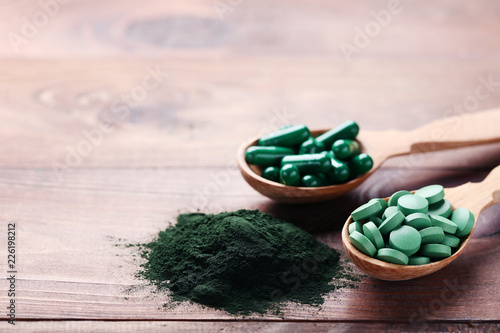 Fotografia  Spirulina powder and tablets in spoons on brown wooden table