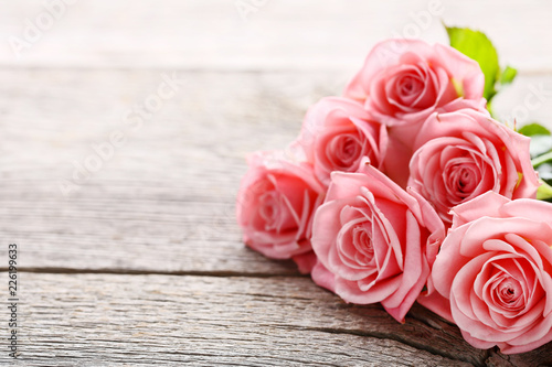 Fotobehang Bloemen Bouquet of pink roses on grey wooden table