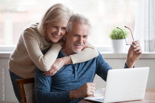 Fototapeta Senior middle aged happy couple embracing using laptop together, smiling elderly