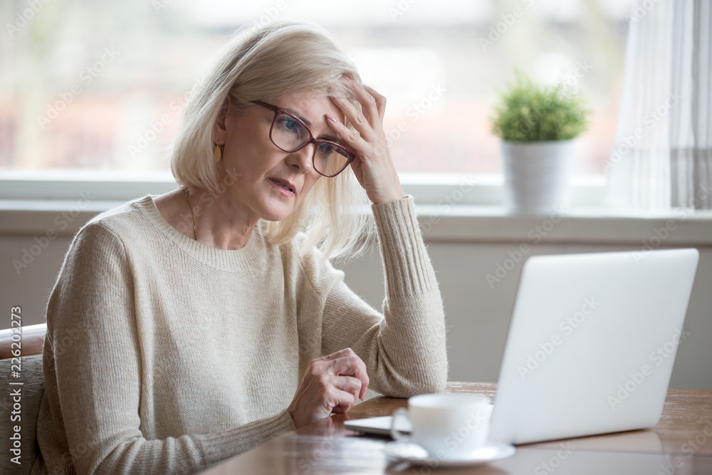Fototapeta Thoughtful confused mature business woman concerned thinking about online problem looking at laptop, frustrated worried senior middle aged female reading bad email news, suffering from memory loss