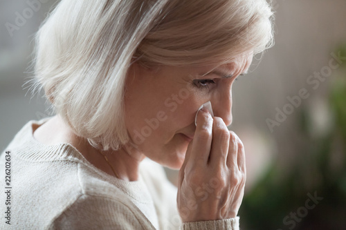 Sad senior middle aged woman widow mourning crying wiping