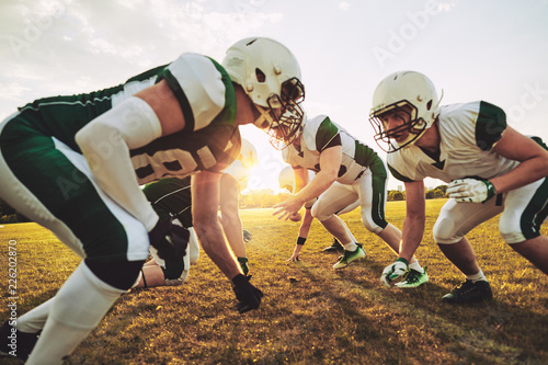 Canvas Print American football players crouching in formation during a team p