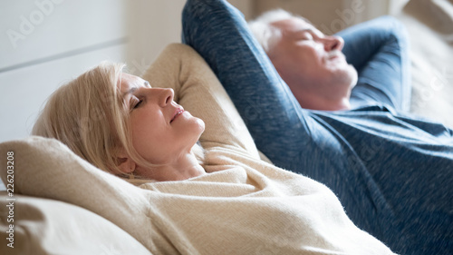 Obraz Senior aged couple relaxing on comfortable sofa together breathing fresh air at home, calm old mature man and woman enjoying no stress free weekend peaceful rest having healthy daytime nap on couch - fototapety do salonu
